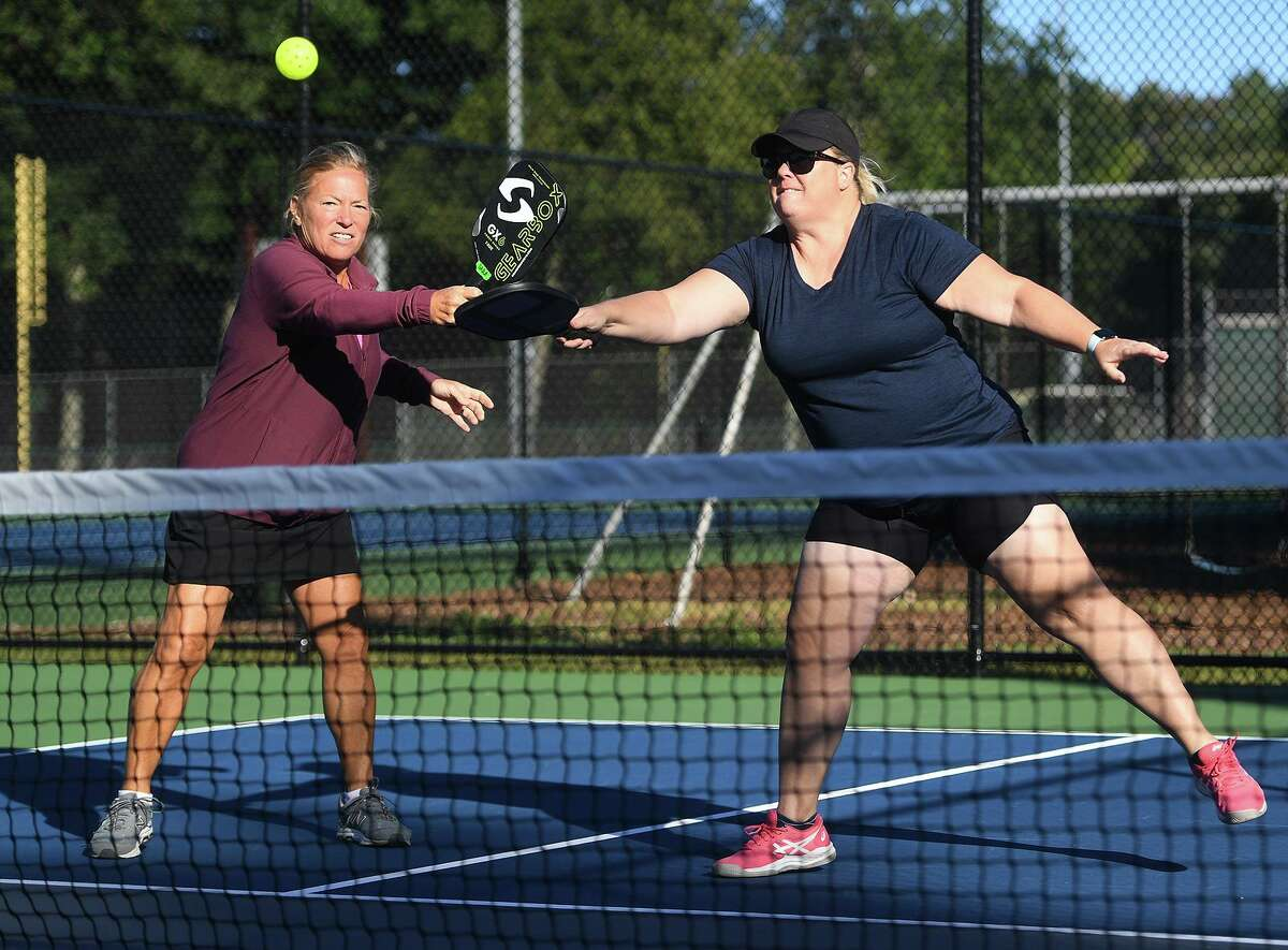 Sara Foster, left, of Trumbull, and Michelle Cox, of Shelton, play pickleball at Unity Park in Trumbull, Conn. on Tuesday, September 29, 20i21.