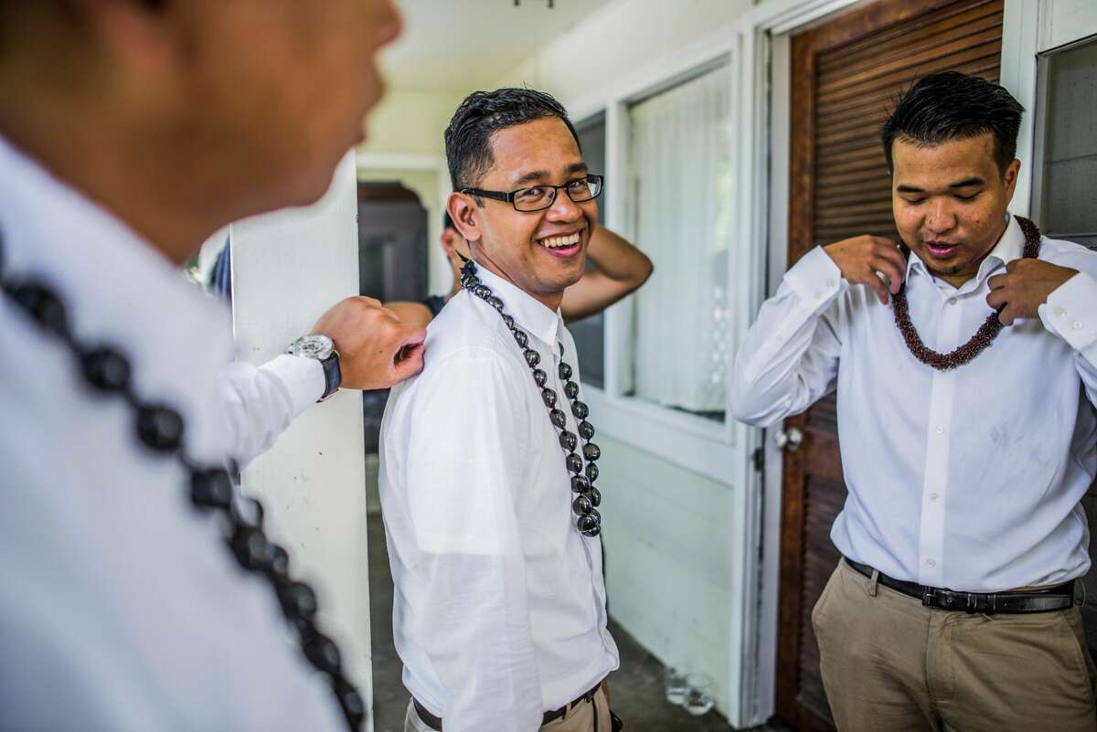 Three young men prepare for a Hawaiian wedding wearing kukui nut beads, Kaaawa, Oahu.