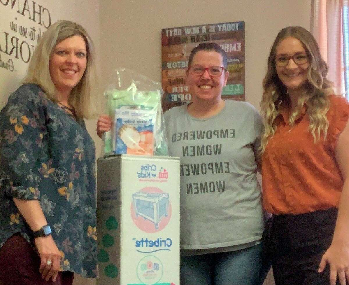 Manistee County Child Advocacy Center family advocate Traci Smith (left) and outreach and prevention specialist Chelsea Medacco (right) give safe sleep donations to nurse midwife Jennifer Cameron of Transitions Women's Wellness Center. (Courtesy photo)