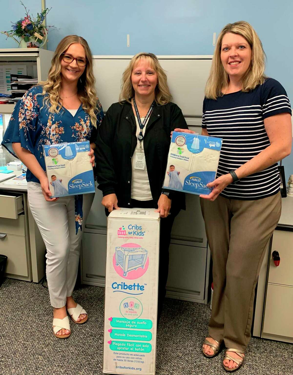 Manistee County Child Advocacy Center outreach and prevention specialist Chelsea Medacco (left) and family advocate Traci Smith (right)present Halo SleepSacks and Cribs for Kids Cribettes to Rebecca Fink of District Health Department #10's maternal infant health program. (Courtesy photo)