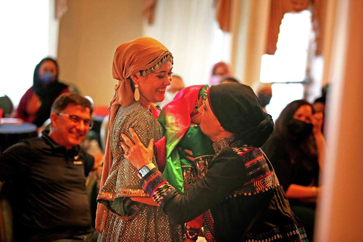 Models Sarah Pearose and her niece get a hug from Sarah's grandmother Sima Pearose. Catholic Charities organized the fashion show featuring Afghan immigrants held Friday, Oct. 1, 2021, at the Woman's Club of San Antonio.