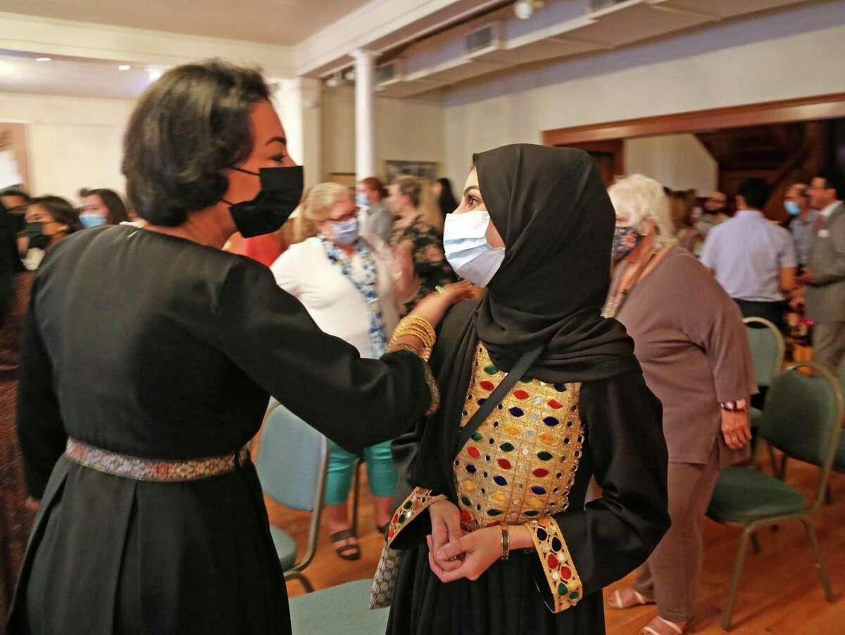Model Mashall Abdalaal, left, thanks seamstress Tamana Haidari, who made the dress Abdalaal wore during the fashion show Friday evening at the Woman's Club of San Antonio. on Friday, Oct. 1, 2021.