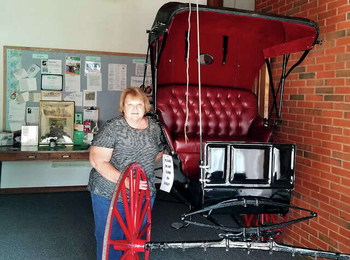 Longtime church member Ruth Klenke stands with her family buggy on display at Immanuel UCC in celebration of its 150th anniversary.