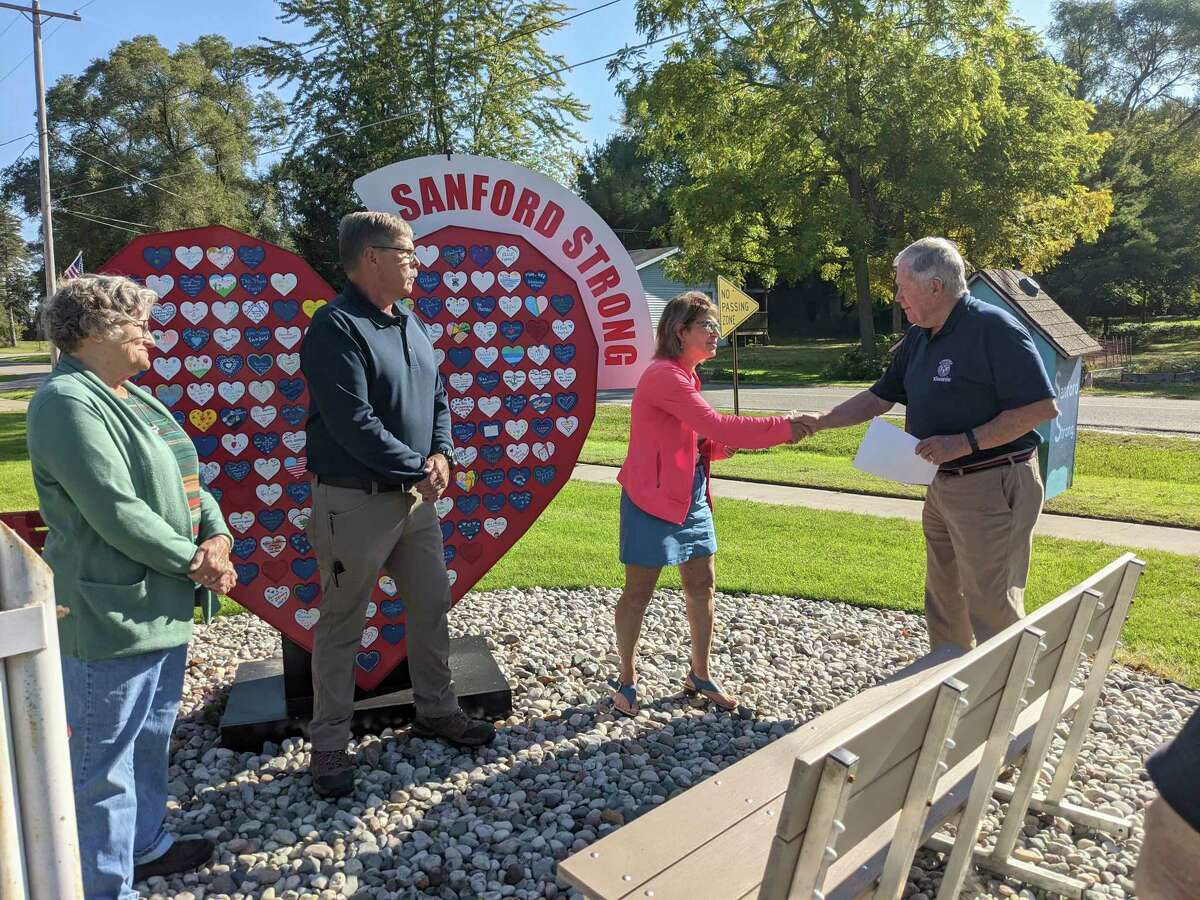 Kiwassee Kiwanis President Bruce Rayce, right, presents a check to Sanford Village President Dolores Porte for the purchase of picnic tablesfor the Village Park in honor of longtime Sanford resident and Kiwanis member Roger Briggs. The park was largely destroyed in the flooding. Pictured along with Rayce and Porte are Jerome Township Fire Chief Jerry Cole and Briggs's wife Martha, far left. (Tereasa Nims/for the Daily News)