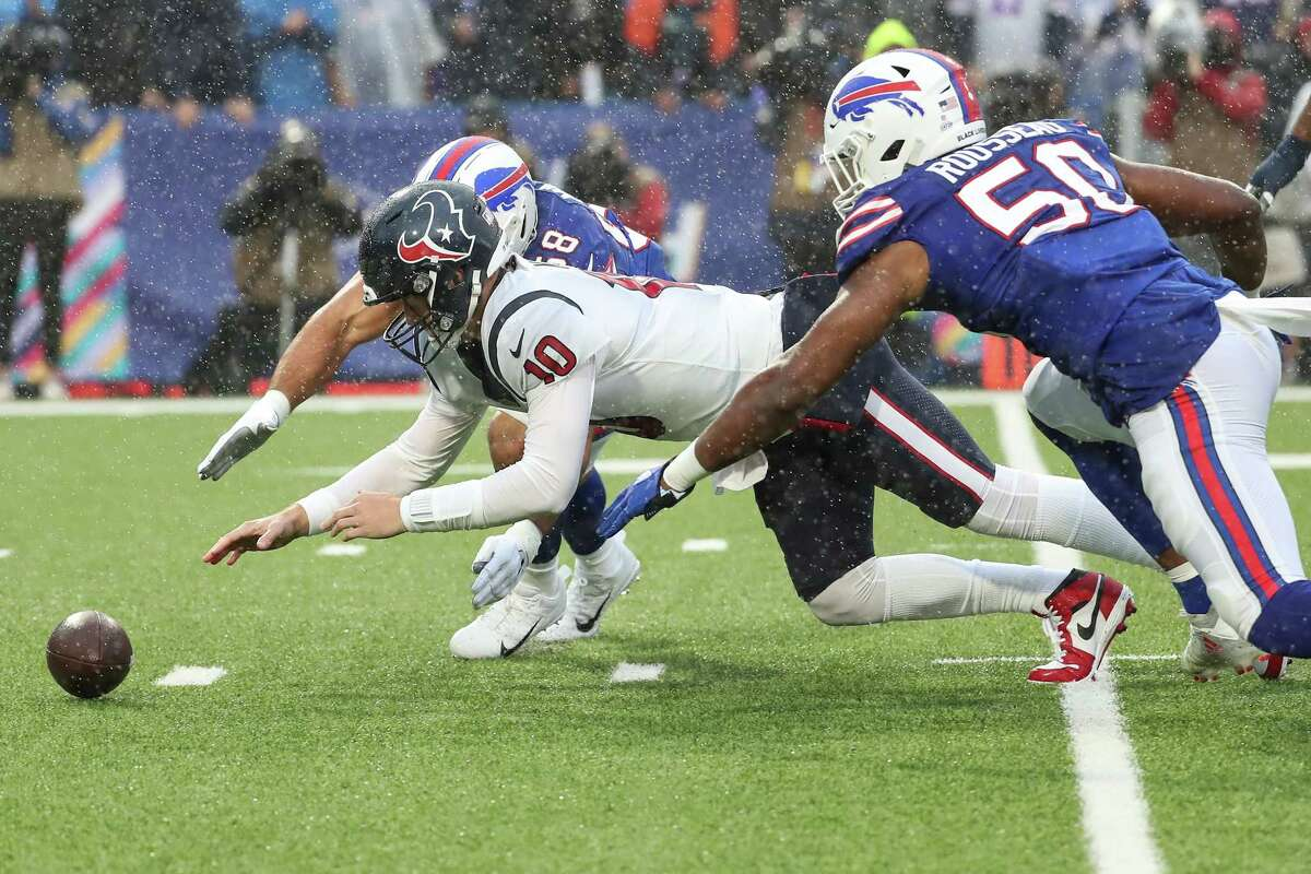 Houston Texans quarterback Davis Mills (10) dives on his own fumble ahead of Buffalo Bills defensive end Greg Rousseau (50) during the first half of an NFL football game Sunday, Oct. 3, 2021, in Orchard Park, N.Y..