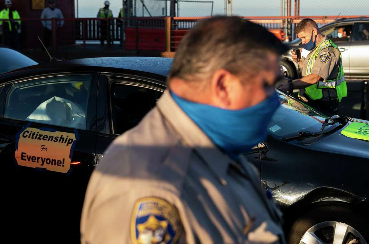 Officers confiscate the keys of protesters cars as they block northbound traffic during an immigration demonstration Thursday on the Golden Gate Bridge.