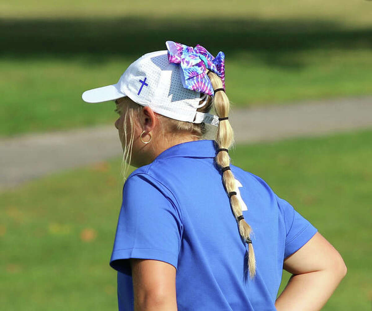 Marquette Catholic's Audrey Cain sports the bow worn by the Explorers during their school-record 306 to win the Class 1A regional at Belk Park golf course in Wood River. The bows, the pay off for a lost bet, will be back with the Explorers on Monday in the sectional at Acorns in Waterloo.