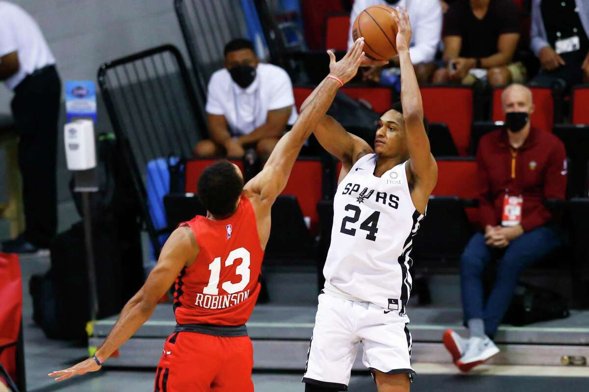 San Antonio Spurs' Devin Vassell (24) shoots as Chicago Bulls' Jerome Robinson (13) defends during the first half of an NBA summer league basketball game in Las Vegas on Tuesday, Aug. 10, 2021. (AP Photo/Chase Stevens)