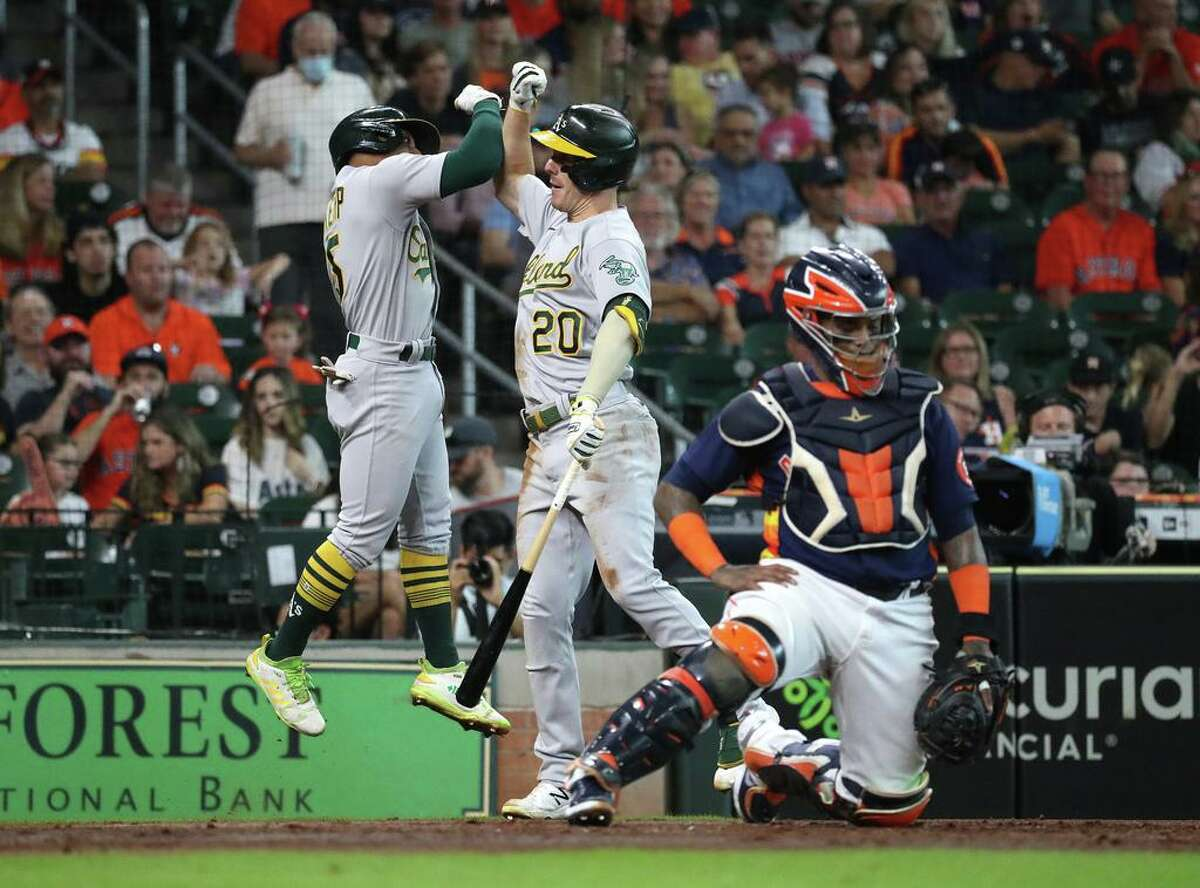 Oakland Athletics Tony Kemp celebrates with Mark Canha (20) after his home run off Houston Astros starting pitcher Jose Urquidy during the third inning of an MLB baseball game at Minute Maid Park, Sunday, October 3, 2021, in Houston.