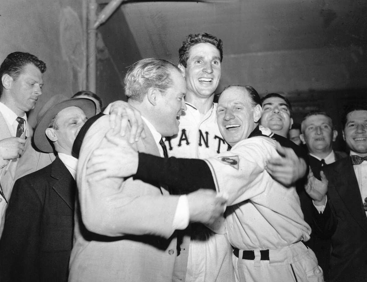 """The New York Giants' Bobby Thomson (center) gets a hug from owner Horace Stoneham (left) and manager Leo Durocher after """"The Shot Heard 'Round the World"""" on Oct. 3, 1951."""