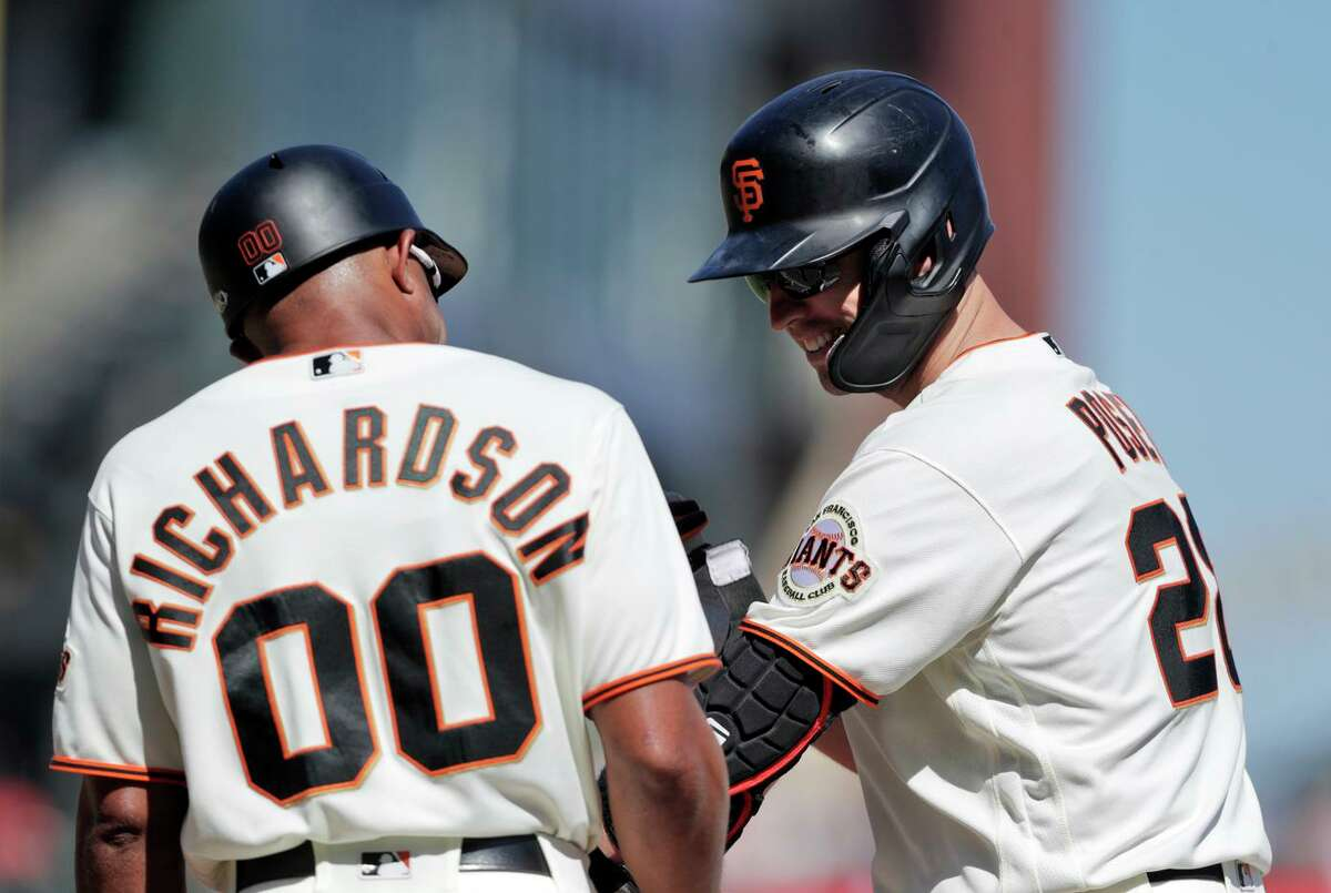 Buster Posey smiles at first base coach Antoan Richardson after hitting his 1500th career hit in the fourth inning.