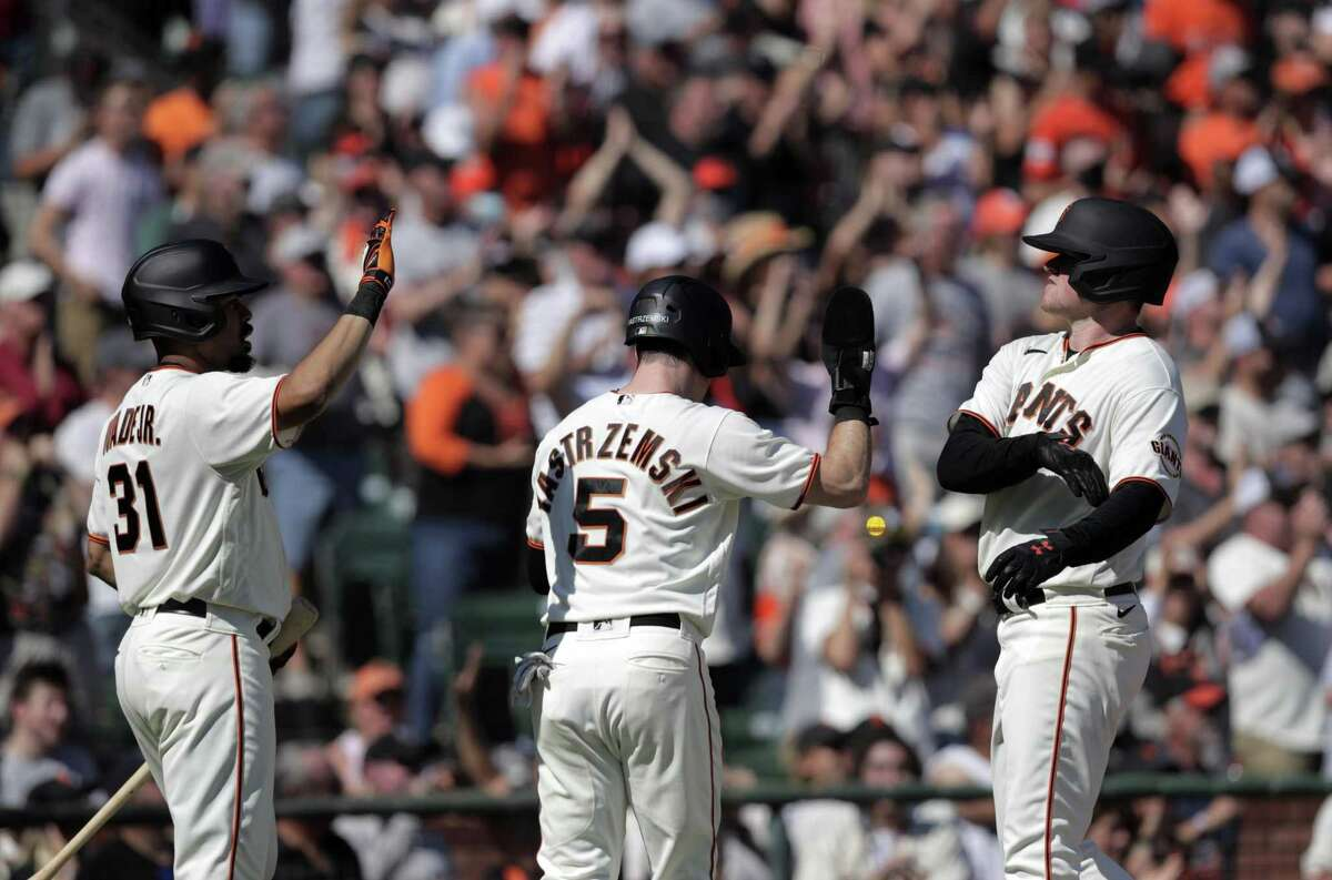 LaMonte Wade Jr. high fives Mike Yastrzemski and Logan Webb after they scored on a double by Wilmer Flores in the fourth inning.