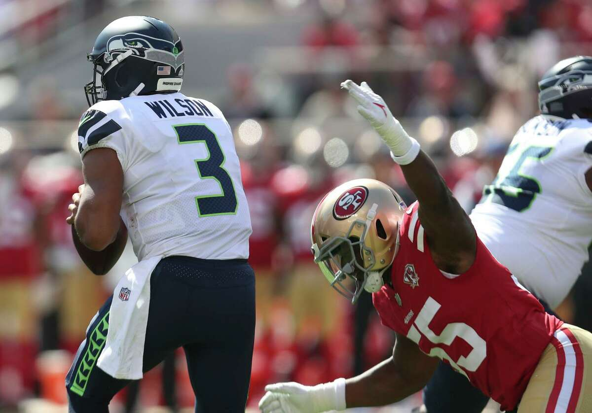 San Francisco 49ers defensive end Dee Ford (55) reaches to sack Seattle Seahawks quarterback Russell Wilson (3) during the first half of an NFL football game in Santa Clara, Calif., Sunday, Oct. 3, 2021. (AP Photo/Jed Jacobsohn)