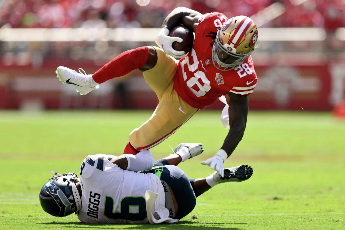 SANTA CLARA, CALIFORNIA - OCTOBER 03: Trey Sermon #28 of the San Francisco 49ers dives over Quandre Diggs #6 of the Seattle Seahawks during the first quarter at Levi's Stadium on October 03, 2021 in Santa Clara, California. (Photo by Ezra Shaw/Getty Images)