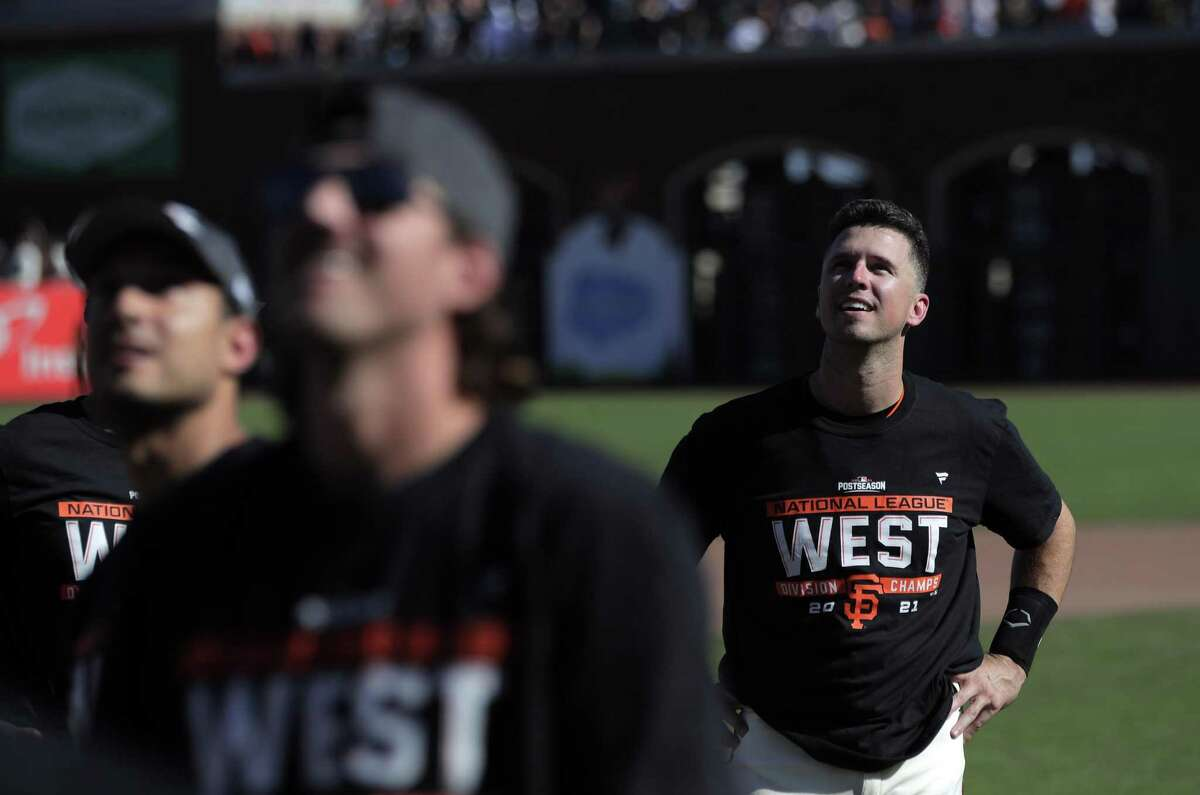 Buster Posey watches as teammates throw baseballs to fans as the Giants celebrate on the field after they defeated the Padres 11-4 to win the National League West at Oracle Park, October 3, 2021.