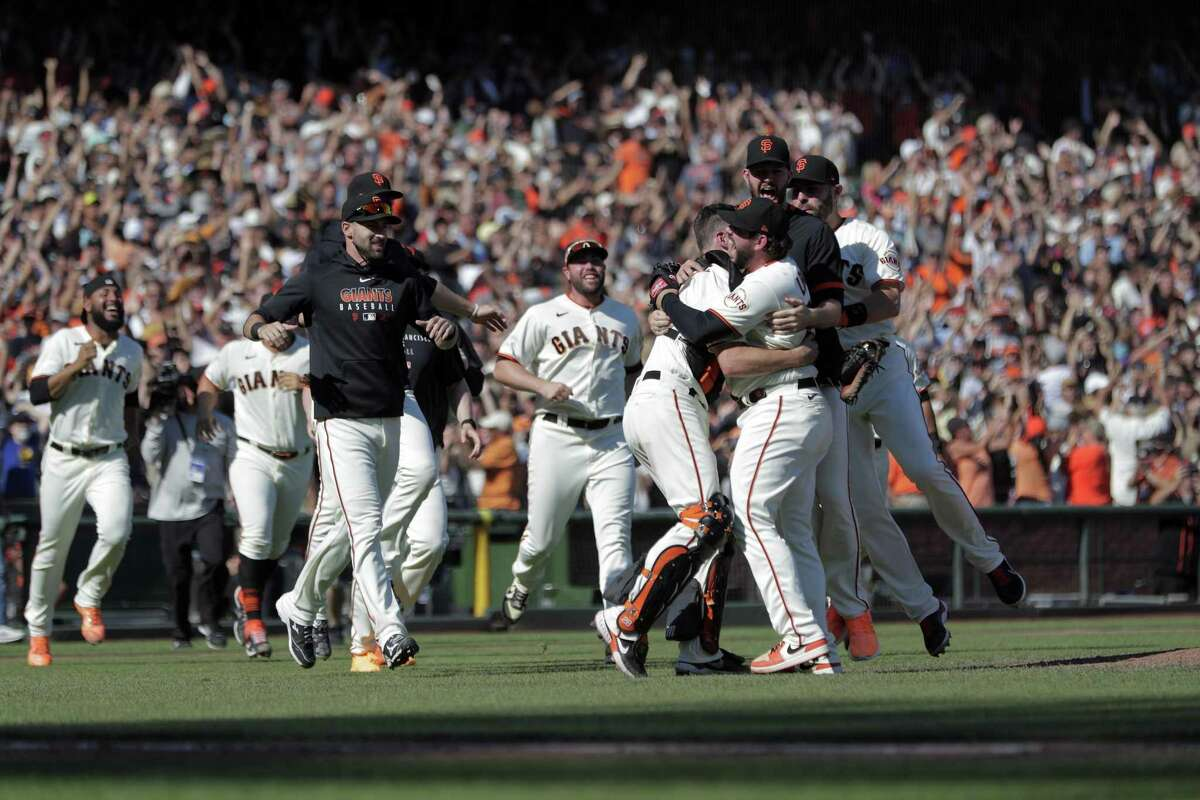 Buster Posey hugs pitcher Dominic Leone as they get mobbed by teammates after striking out Eric Hosmer for the final out against the San Diego Padres to win the National League West at Oracle Park in San Francisco, on Sunday, October 3, 2021.