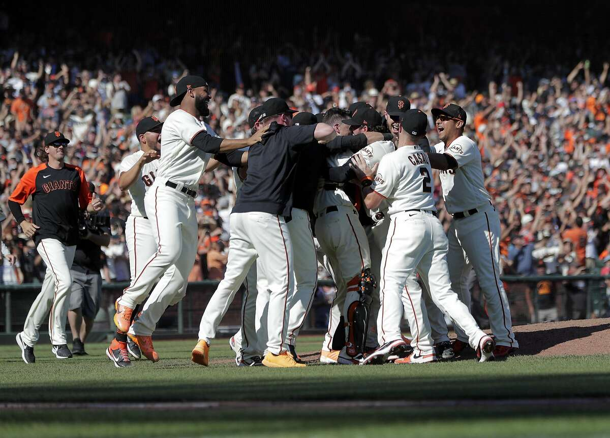 The Giants celebrate on the field after they defeated the Padres 11-4 to win the National League West at Oracle Park in San Francisco on Sunday, October 3, 2021.