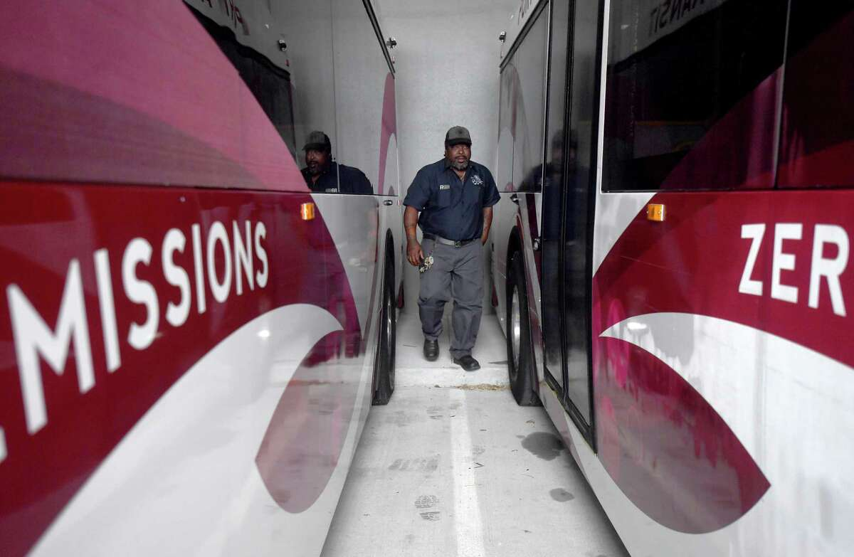 Port Arthur Transit maintenance supervisor Anthony Grogan walks between buses in the charging/parking stations for its growing fleet of zero emission all electric buses. Photo made Friday, October 1, 2021 Kim Brent/The Enterprise