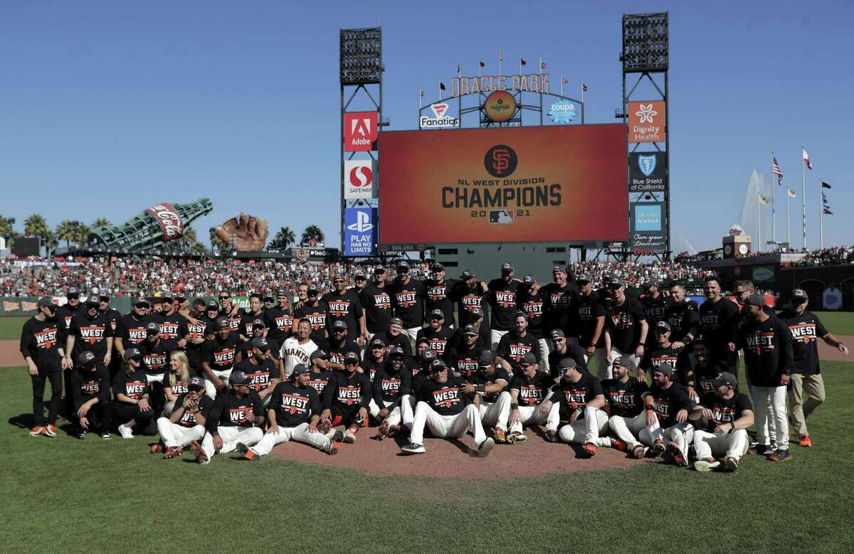 The San Francisco Giants pose for a team photo as they celebrate on the field after they defeated the San Diego Padres 11-4 to win the National League West at Oracle Park in San Francisco, Calif., on Sunday, October 3, 2021.