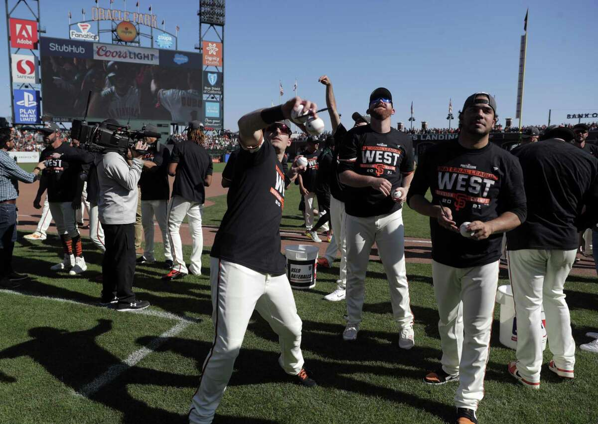 Mike Yastrzemski throws a ball to the fans as the San Francisco Giants celebrate on the field after they defeated the San Diego Padres 11-4 to win the National League West at Oracle Park in San Francisco on Sunday.