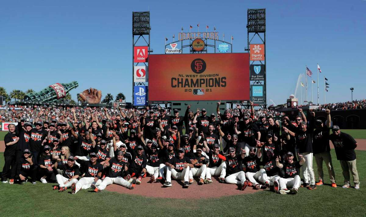 The Giants pose for a team picture as they celebrate after defeating the Padres 11-4 to win the National League West at Oracle Park in San Francisco on Sunday.