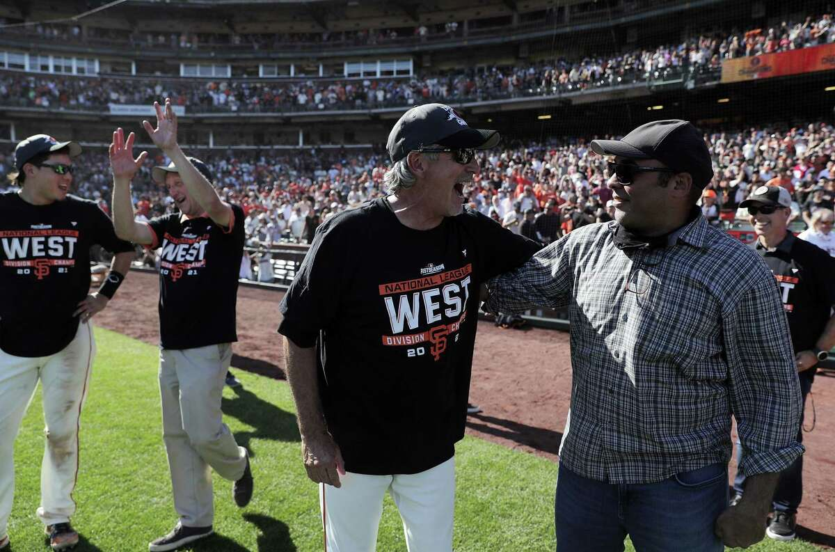 Ron Wotus laughs with Giants President Farhan Zaidi as the San Francisco Giants celebrate on the field after they defeated the San Diego Padres 11-4 to win the National League West at Oracle Park in San Francisco, Calif., on Sunday, October 3, 2021.