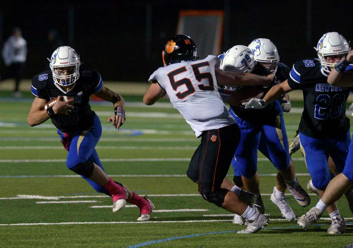 Newtown's Dylan Magazu (16) tries to get outside of Ridgefield's Nicholas Masi (55) in the high school football game between Ridgefield and Newtown high schools. Friday night, October 1, 2021, at Newtown High School, Newtown, Conn.
