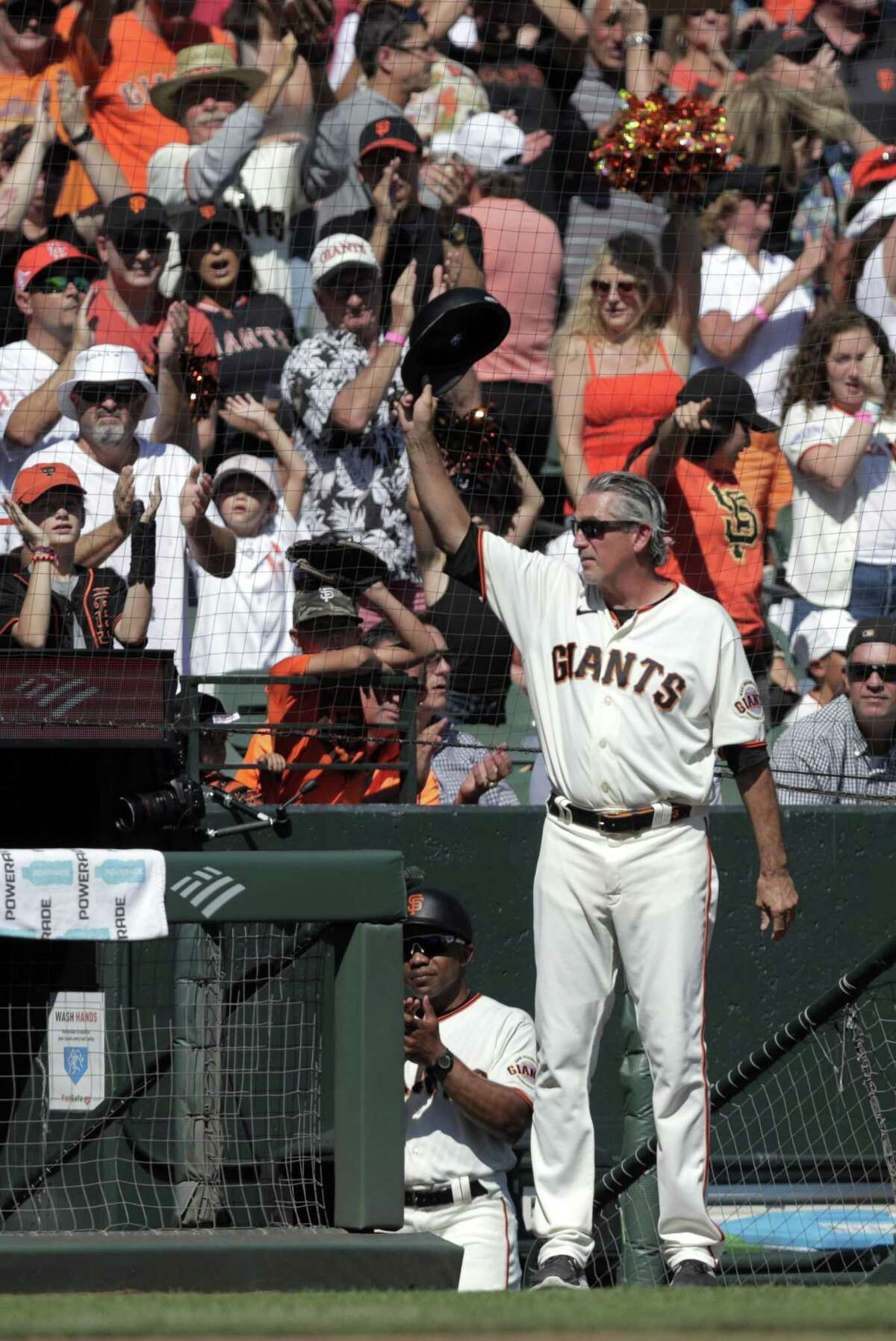 Giants third base coach Ron Wotus (8) tips his cap to the fans after he was honored by the team in the fourth inning as the San Francisco Giants played the San Diego Padres at Oracle Park in San Francisco, Calif., on Sunday, October 3, 2021.