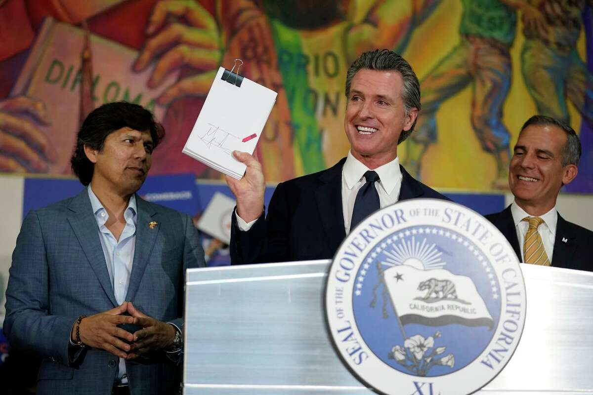 Gov. Gavin Newsom rejoices after signing the California Comeback Plan in July alongside Los Angeles City Council Member Kevin de Leon (left) and Mayor Eric Garcetti.