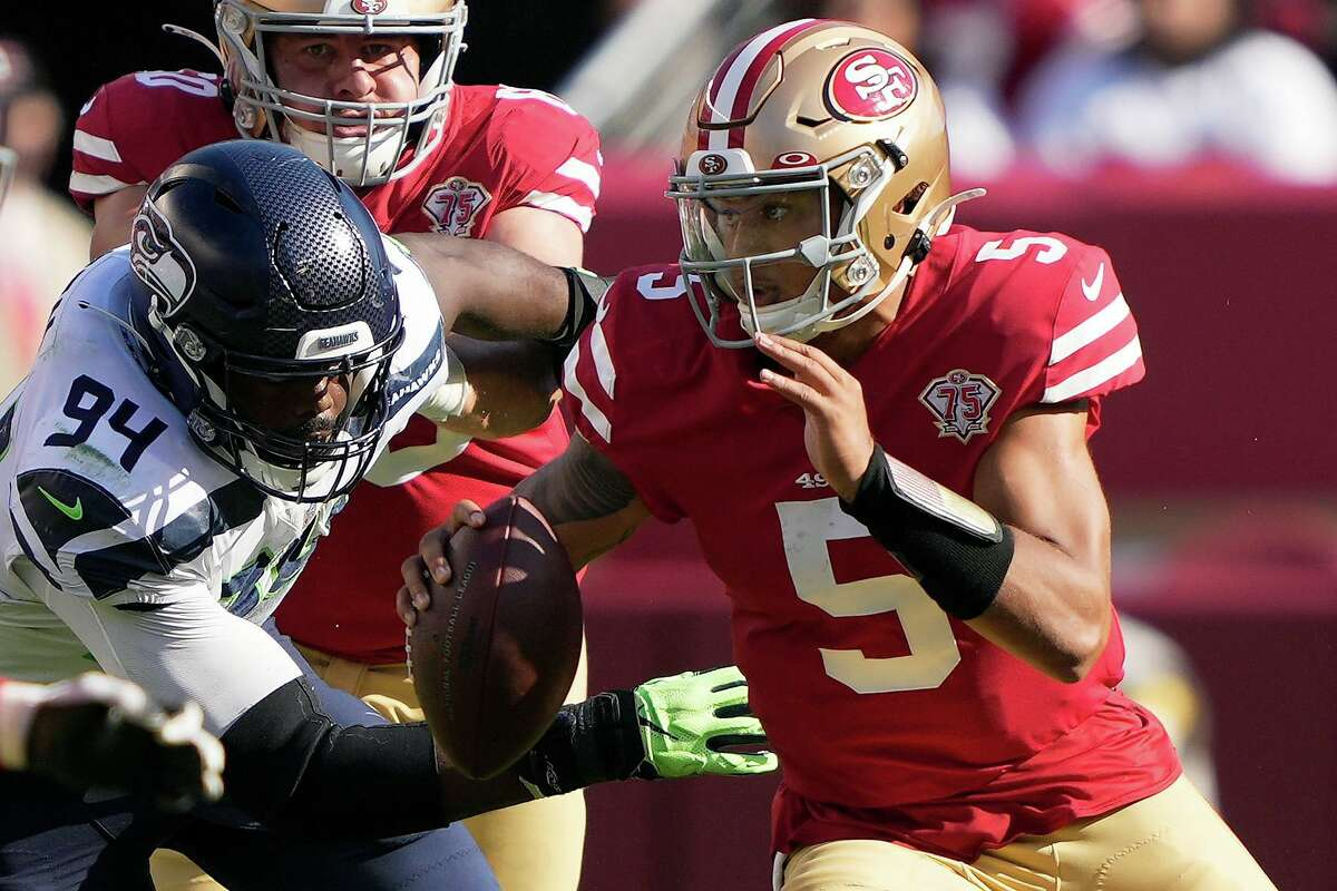 SANTA CLARA, CALIFORNIA - OCTOBER 03: Trey Lance #5 of the San Francisco 49ers scrambles to avoid a tackle by Rasheem Green #94 of the Seattle Seahawks during the second half at Levi's Stadium on October 03, 2021 in Santa Clara, California. (Photo by Thearon W. Henderson/Getty Images)