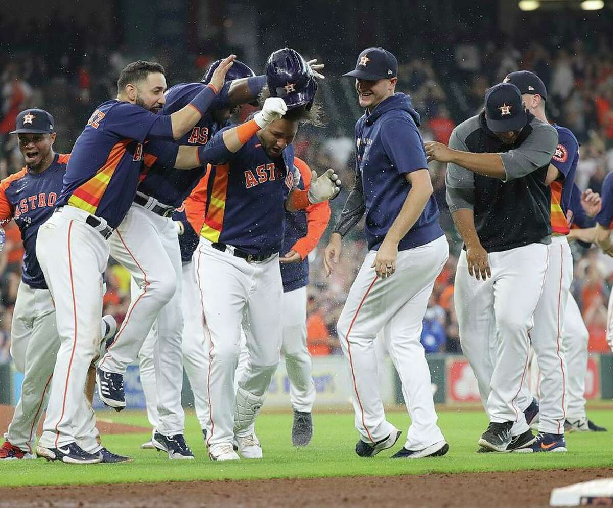 Astros players surround Yuli Gurriel after his game-ending single against the A's Lou Trivino in the ninth inning.