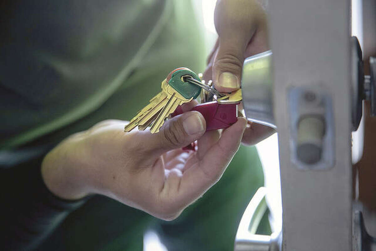 An apartment maintenance man changes the lock of an apartment after constables posted an eviction order.