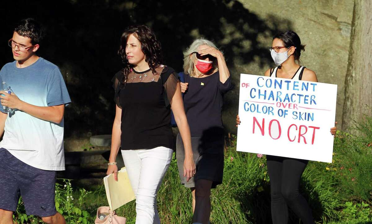 A woman carrying a sign protesting the teaching of critical race theory arrives at a Board of Education meeting at Central Middle School in Greenwich, Conn., on Thursday June 17, 2021. Members of the group Greenwich Patriots came out to the meeting to urge people to attend and speak at public comment to protest masking, vaccinations for students and critical race theory.