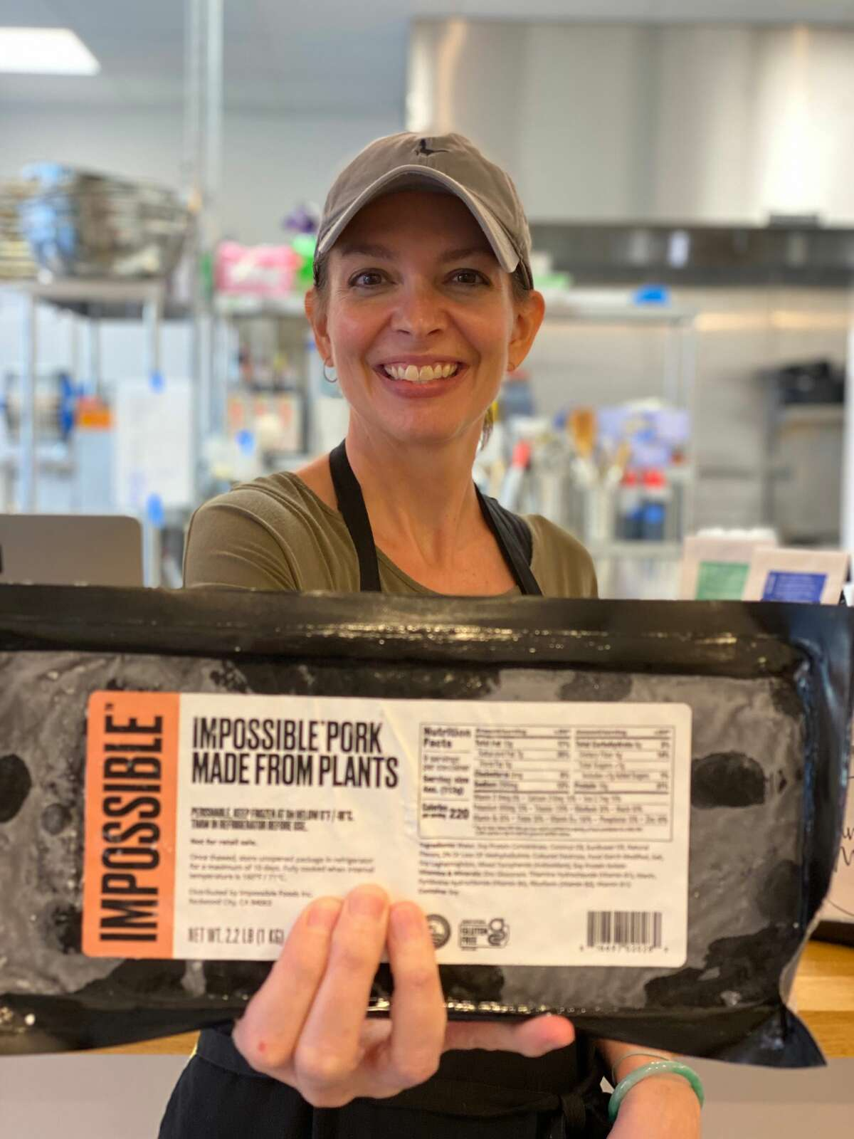 """Stacy Nguyen, who owns Banh MI 47 in Albany with her husband, Mike, holds a package of Impossible Foods new plant-based """"pork"""" product."""