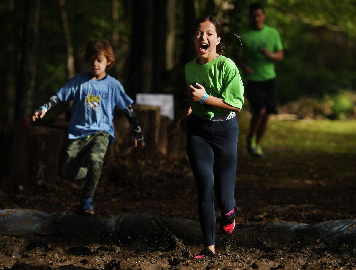 Runners cross the first of several mud pits during the ninth annual Muddy Up 5k run put on by the Boys and Girls Club of Greenwich at Camp Simmons in Greenwich on Sunday.
