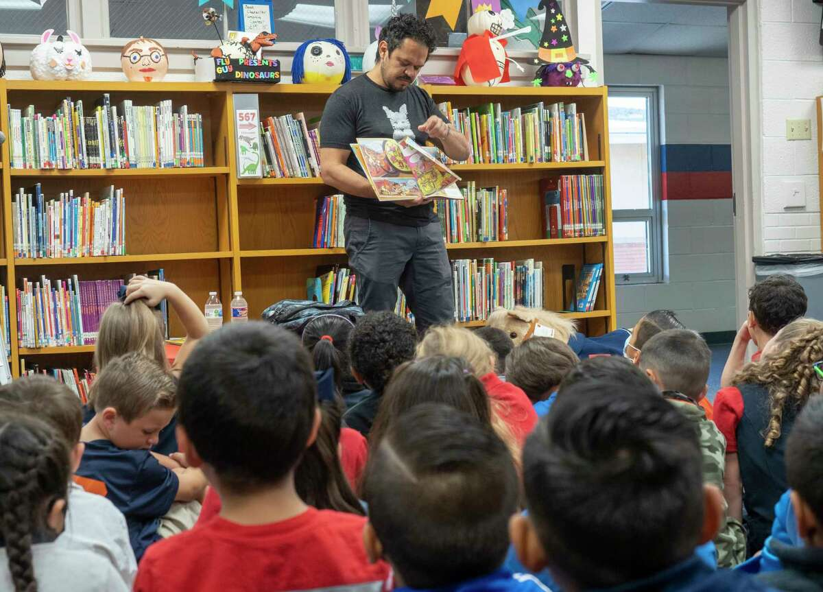 Author, Raul the Third, reads one of his books, Vamos! Let's Cross the Bridge, and demontrates how he draws the characters for first and second graders at Washington STEM Academy to kick off Project Literacy 10/04/2021 at Washington STEM Academy. Tim Fischer/Reporter-Telegram