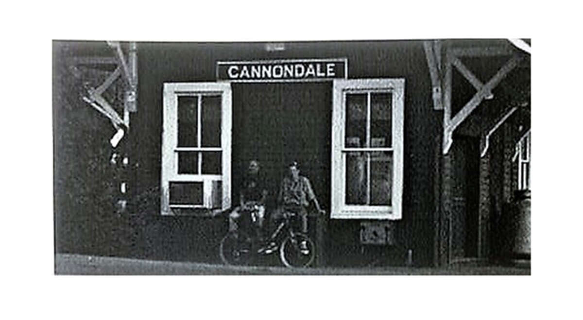 """On a photo from the book """"Cannondale, handmade in the USA,"""" company founder Joe Montgomery and his son Scott stand outside Cannondale station in 1996."""