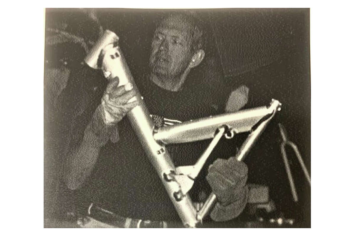 """On a photo from the book """"Cannondale, handmade in the USA,"""" company founder Joe Montgomery holds a bicycle frame in 1997"""
