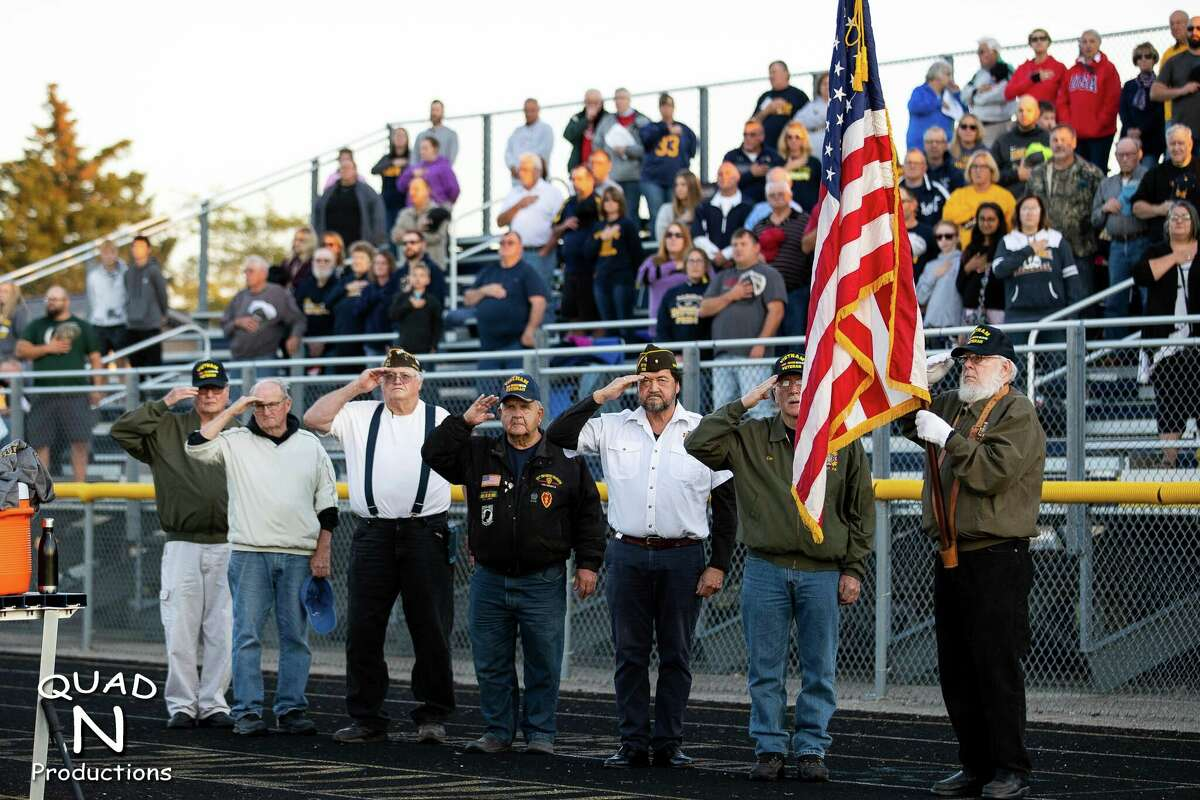 Veterans salute the flag on Military Appreciation night. (Quad N Productions/For the Tribune)