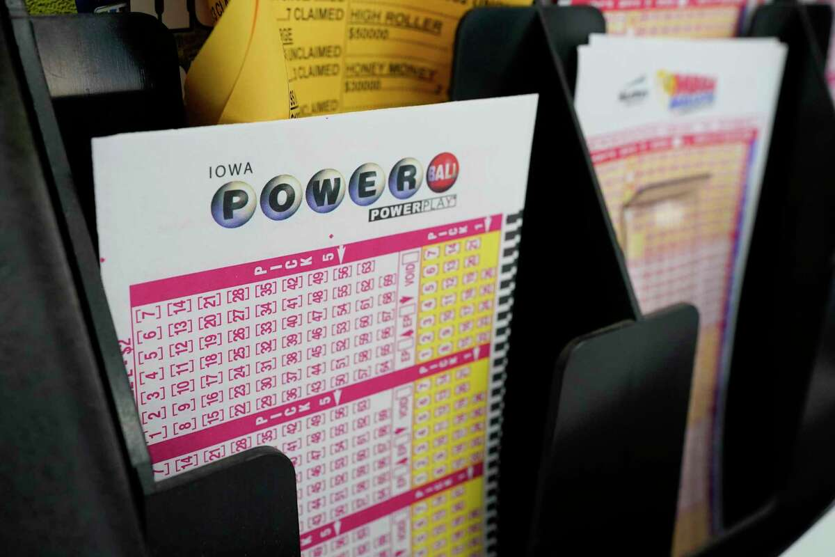FILE - In this Jan. 12, 2021 file photo, blank forms for the Powerball lottery sit in a bin at a local grocery store, in Des Moines, Iowa.