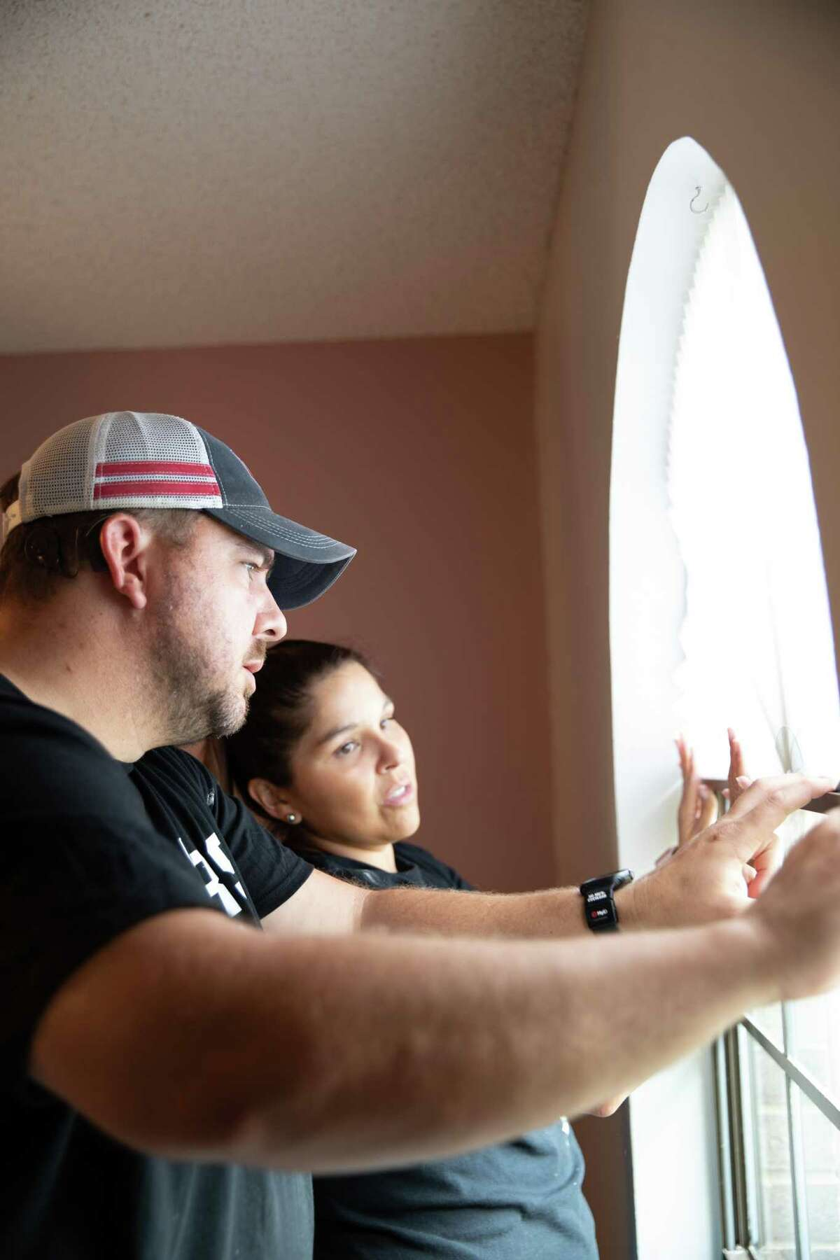 Amanda Fite, Spurs Give youth sports manager, and husband Cory Fite adjust a window as they help renovate a child's room with nonprofit Room Redux.