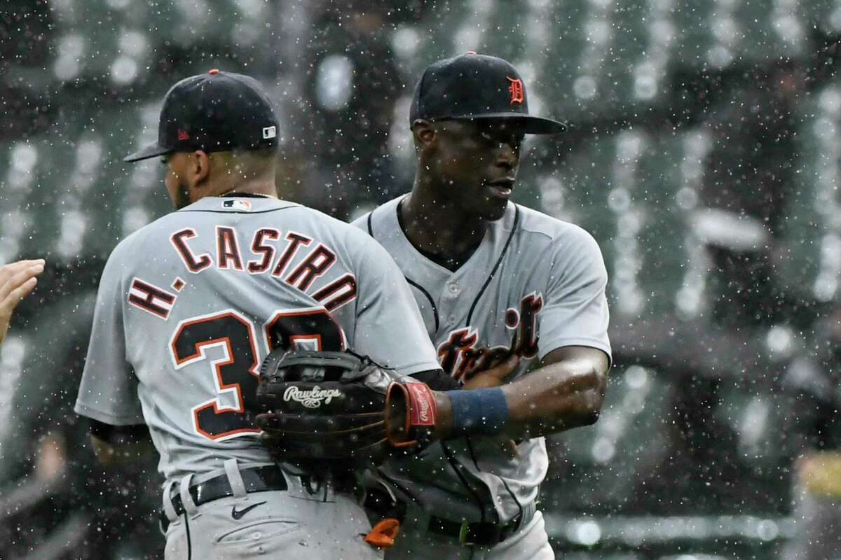 Detroit Tigers second baseman Harold Castro (30) and center fielder Daz Cameron, right, react in the rain at the end of a baseball game against the Chicago White Sox, Sunday, Oct. 3, 2021, in Chicago. (AP Photo/Matt Marton)