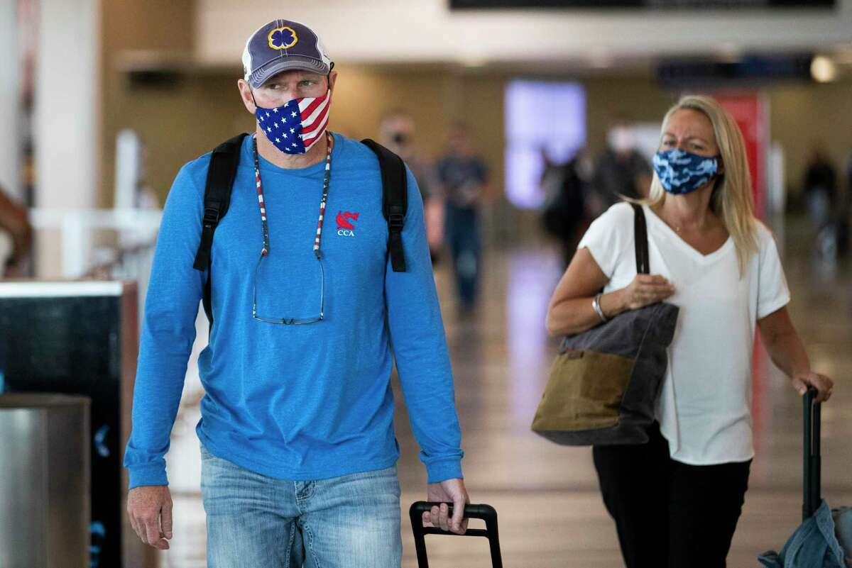 Passengers walk toward the security checkpoint of William P. Hobby Airport wearing protective masks during the COVID-19 pandemic, Thursday, Sept. 17, 2020, in Houston.