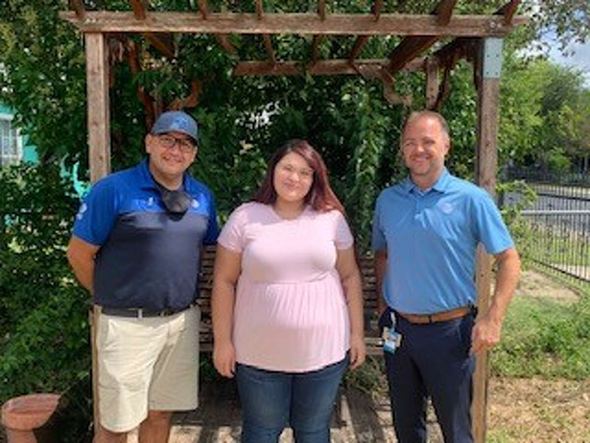 Manny Lopez, Alyssa Dominguez and Michael Pake stand in Dominguez's yard. The two men helped clean up the West Side yard for the busy mother.
