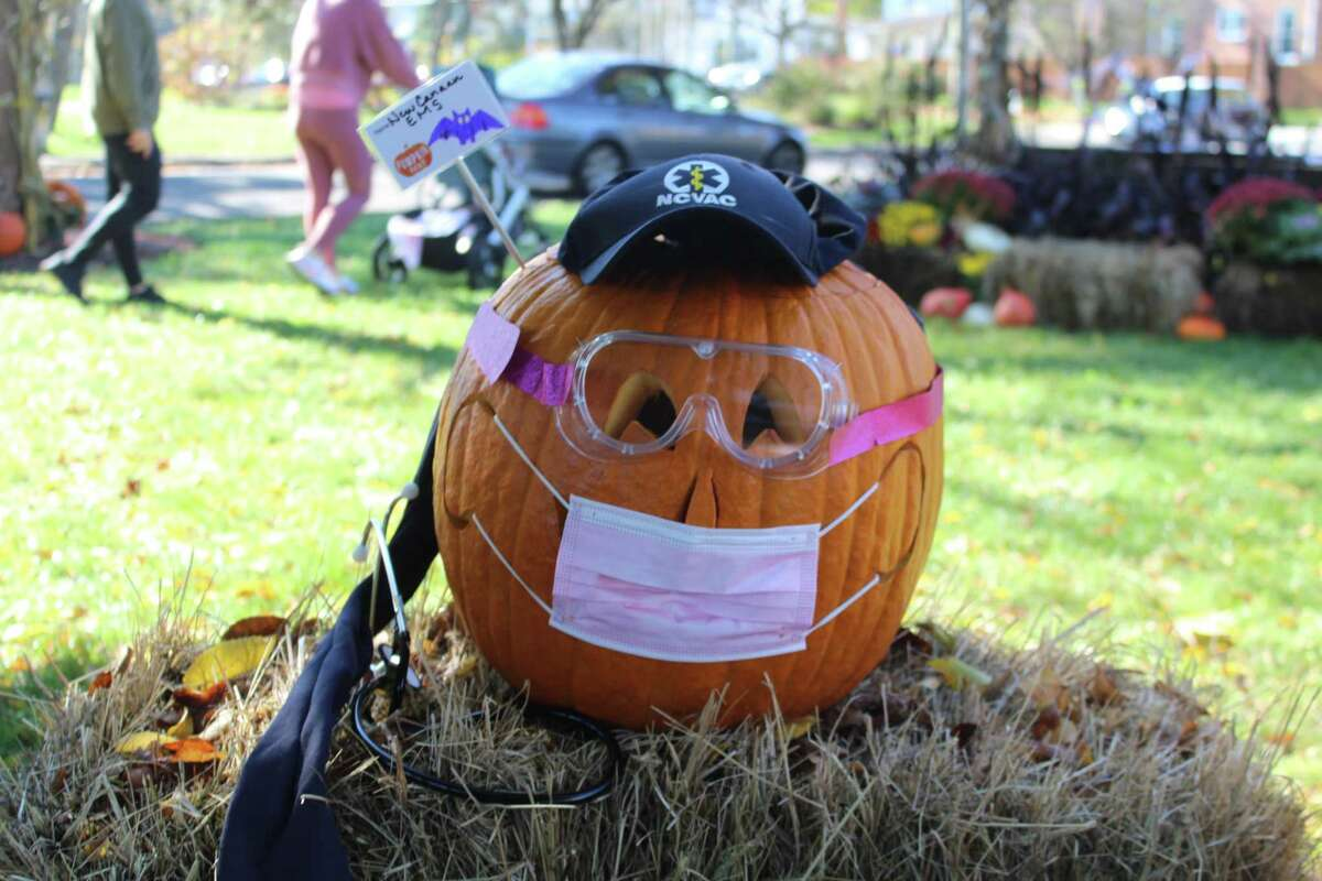 The New Canaan EMS pumpkin at Pumpkin Fest donned a mask and goggles, the protective gear needed on this Halloween during the COVID-19 pandemic.