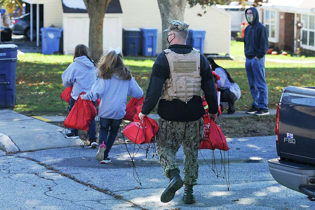 A Sailor assigned to Naval Submarine Base (SUBASE) New London hands out bags of candy as he participates in a Halloween parade for military families in Beacon Point Housing, Oct. 31. The reverse parade was organized by SUBASE New London senior leadership to provide an alternative way for military families to participate in Halloween festivities during the COVID-19 pandemic.
