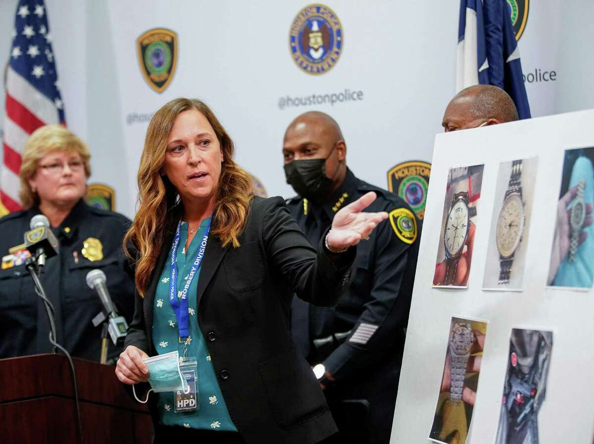 Houston Police officer Catherine Richards points to photographs of items stolen by numerous robbery suspects during a press conference in HPD Headquarters on Monday, Oct. 4, 2021, in Houston.