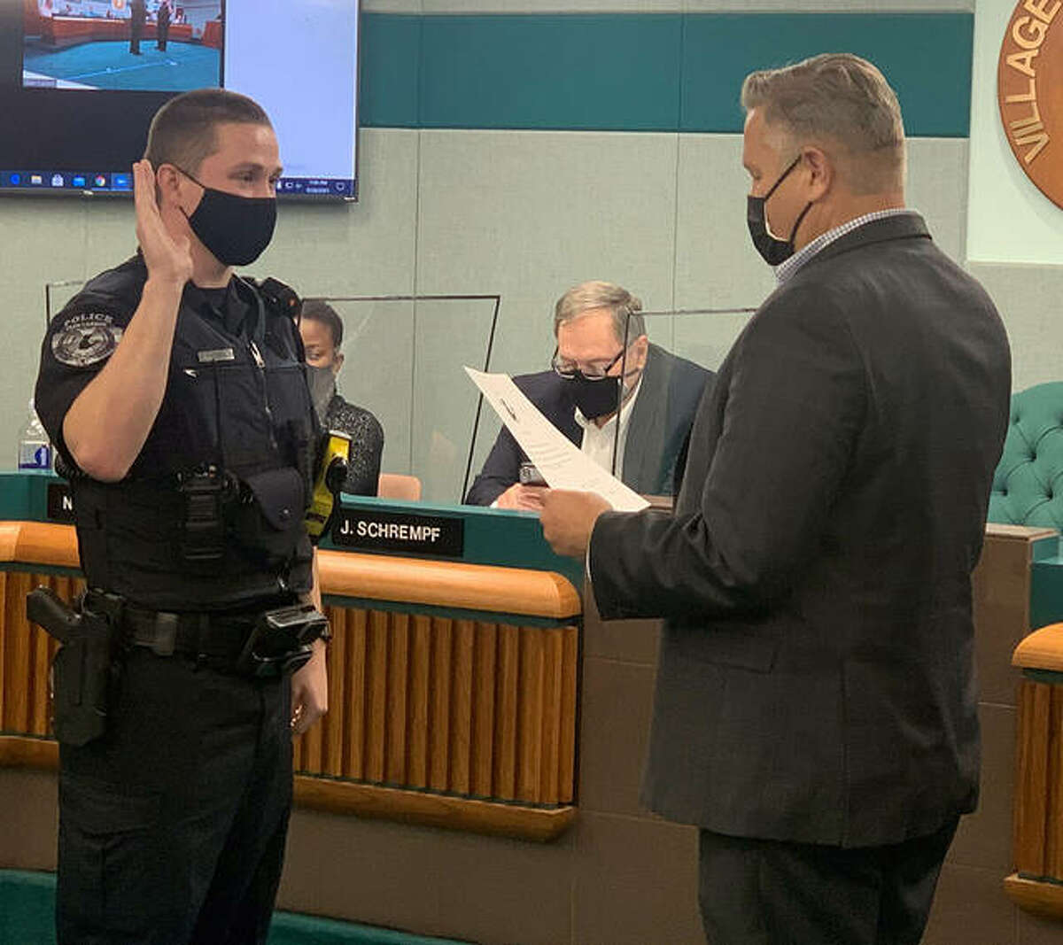 Mayor Bob Marcus, right, gives the oath of allegiance to Zachary Walters, a new police officer, Tuesday.