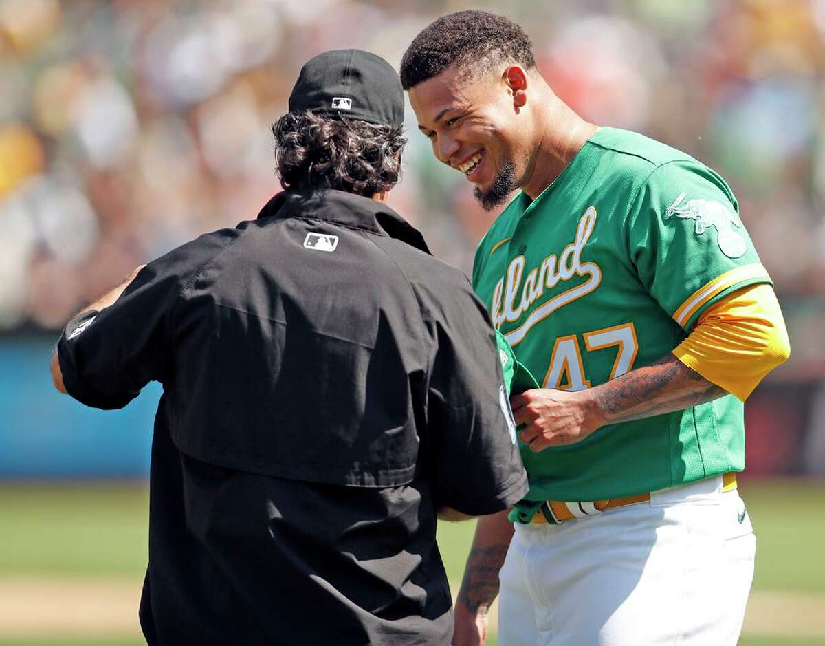 Oakland Athletics' starting pitcher Frankie Montas smiles while having his equipment checked by umpire Phil Cuzzi in 6th inning against San Francisco Giantsduring MLB game at Oakland Coliseum in Oakland, Calif., on Sunday, August 22, 2021.