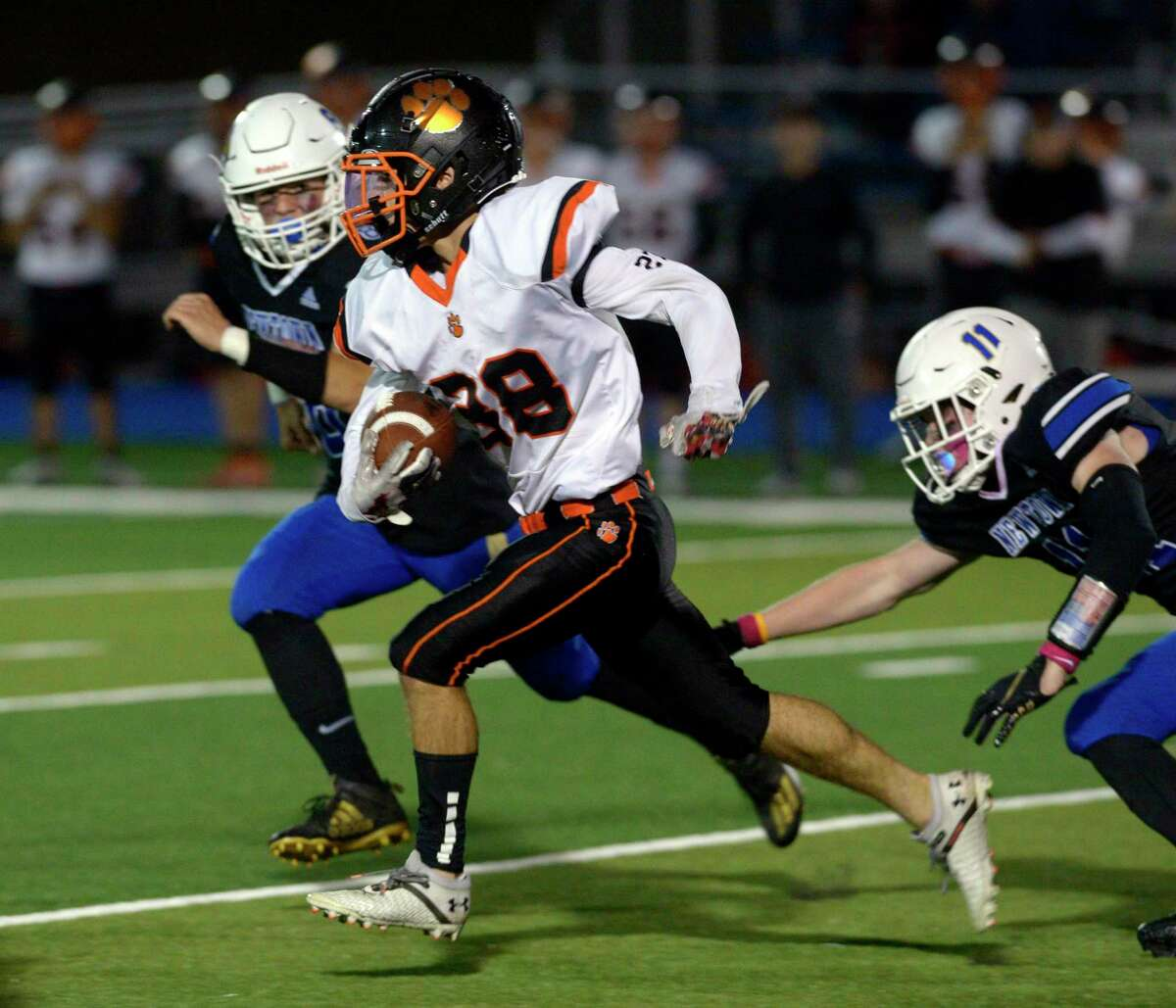 Ridgefield's Matthew Shepard (38) cuts through Newtown's Chris Stowell (8) and Andrew Jacobs (11) for a big gain in the high school football game between Ridgefield and Newtown high schools. Friday night, October 1, 2021, at Newtown High School, Newtown, Conn.